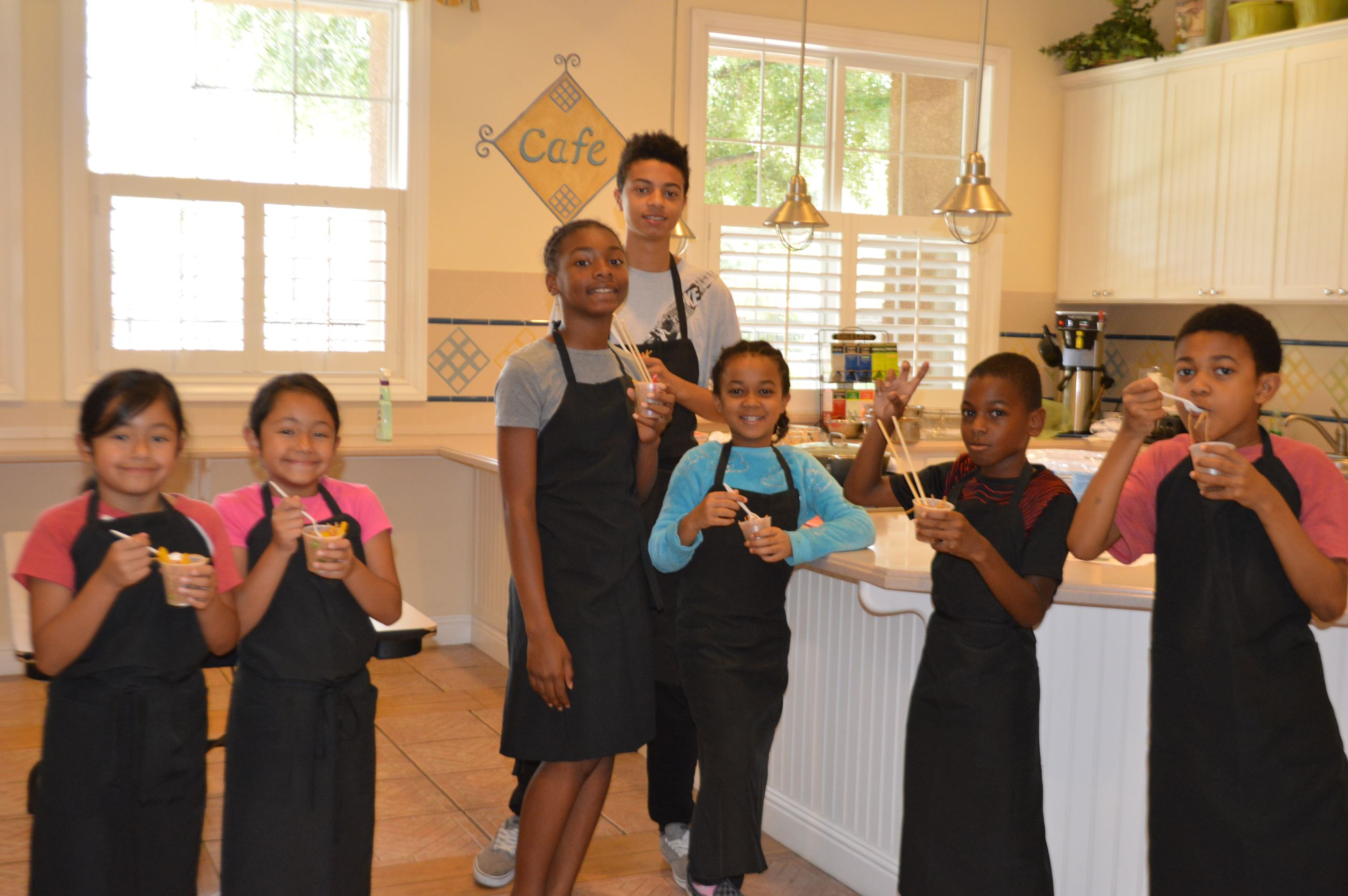 Jr Chef students pose in kitchen holding their food
