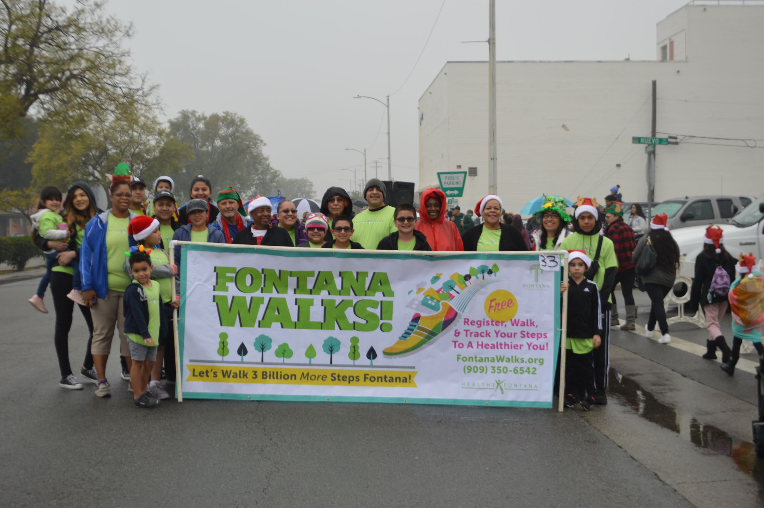 Group holds Fontana Walks banner on rainy day