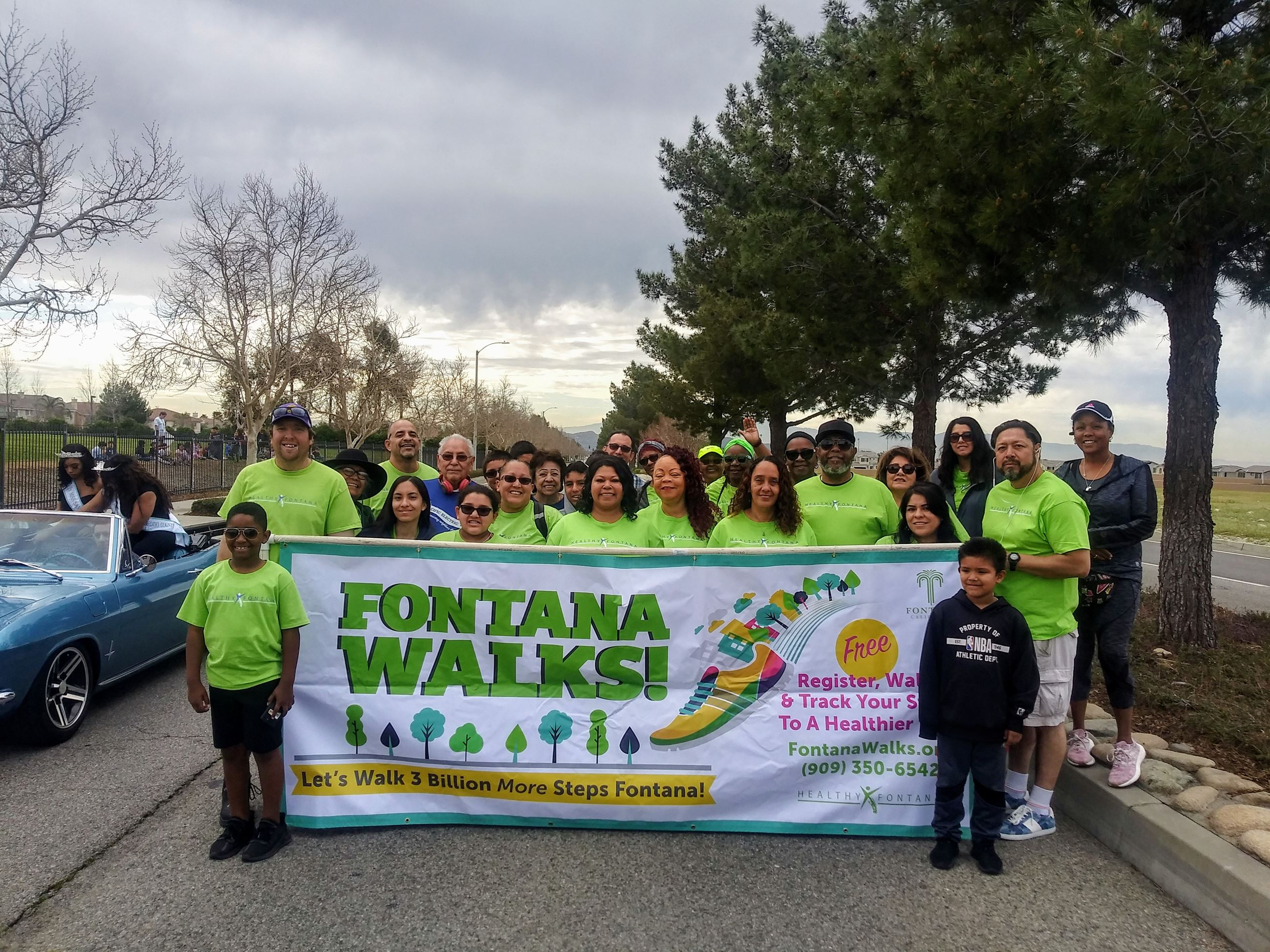 Fontana Walks parade participants holding banner on cloudy day