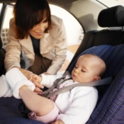 Woman places a baby in a car seat