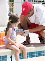 Lifeguard Administering First Aid to Young Girl