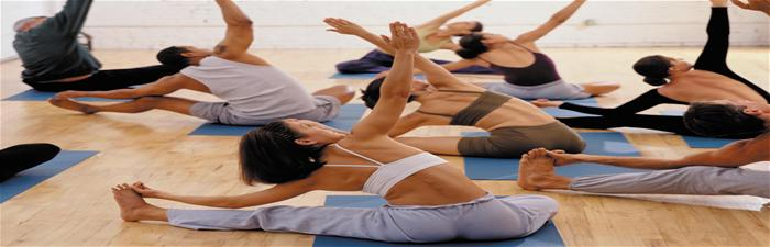 Adults perform poses in yoga class