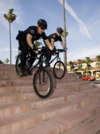Police officers riding bicycles down stairs